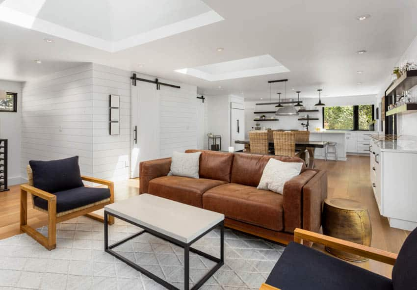 Modern home with brown leather couch white wall tiled floor rattan dining chair and kitchen area