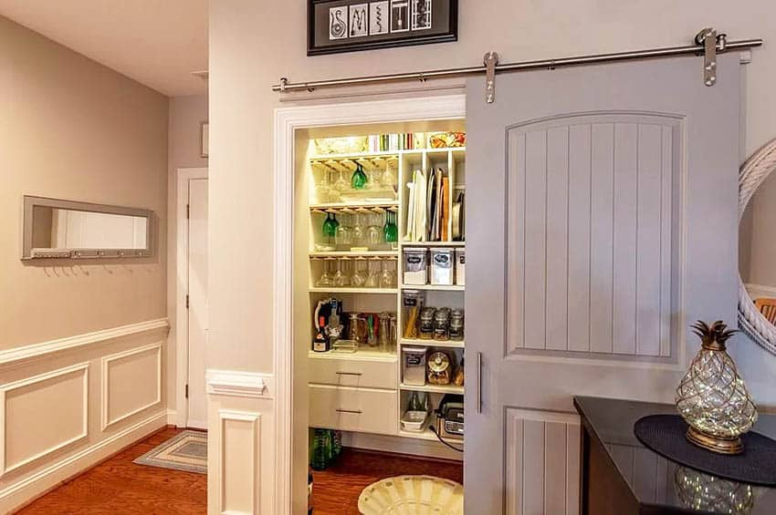 Rolling pantry door with custom storage cabinetry