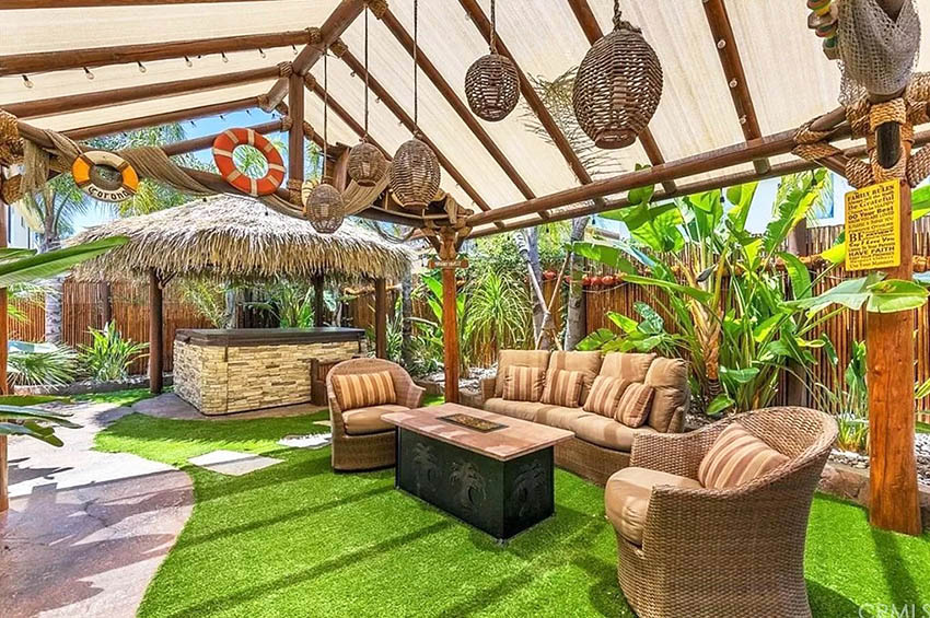 Tropical design patio enclosure with outdoor furniture and tiki bar