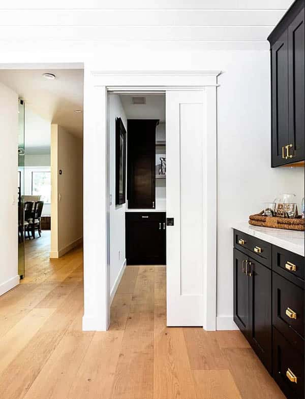 Contemporary kitchen with sliding pocket door to pantry