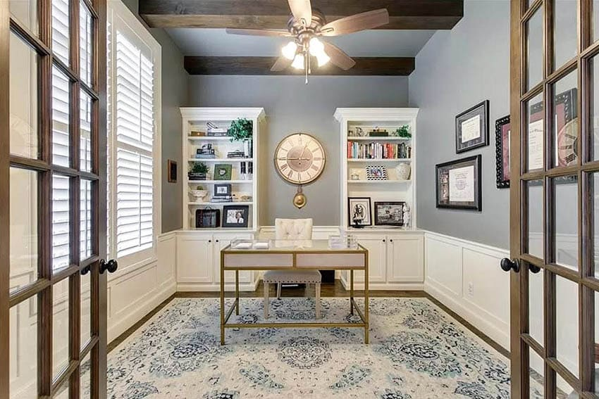 Home office with built in cabinets, white wainscoting and wood french doors