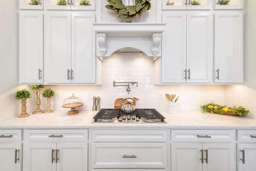 Kitchen countertop with outlets, white cabinets, subway tile backsplash and range hood