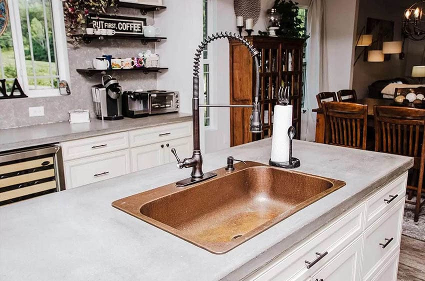 Kitchen island with concrete counter and copper sink