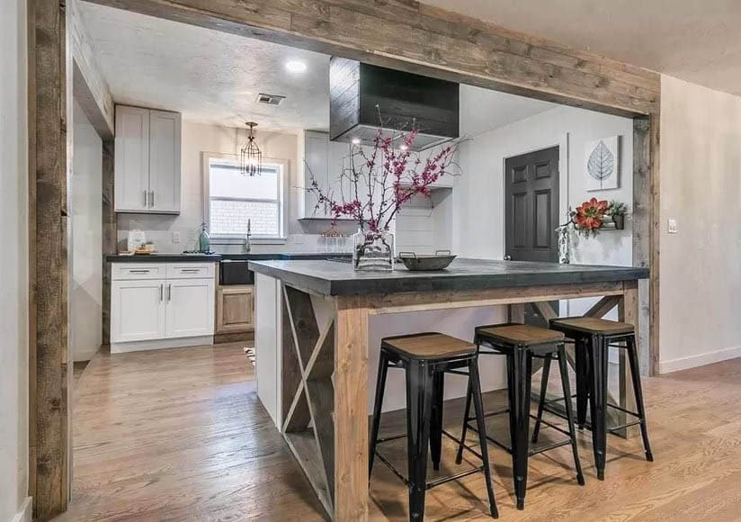 Kitchen with black concrete countertop island and white cabinets with wood beam