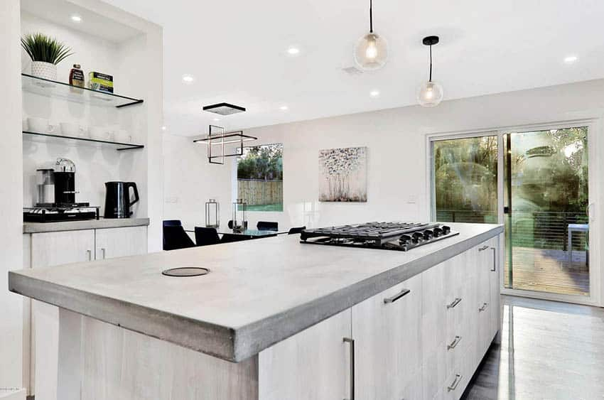 Kitchen with concrete countertop island and bleached wood cabinets