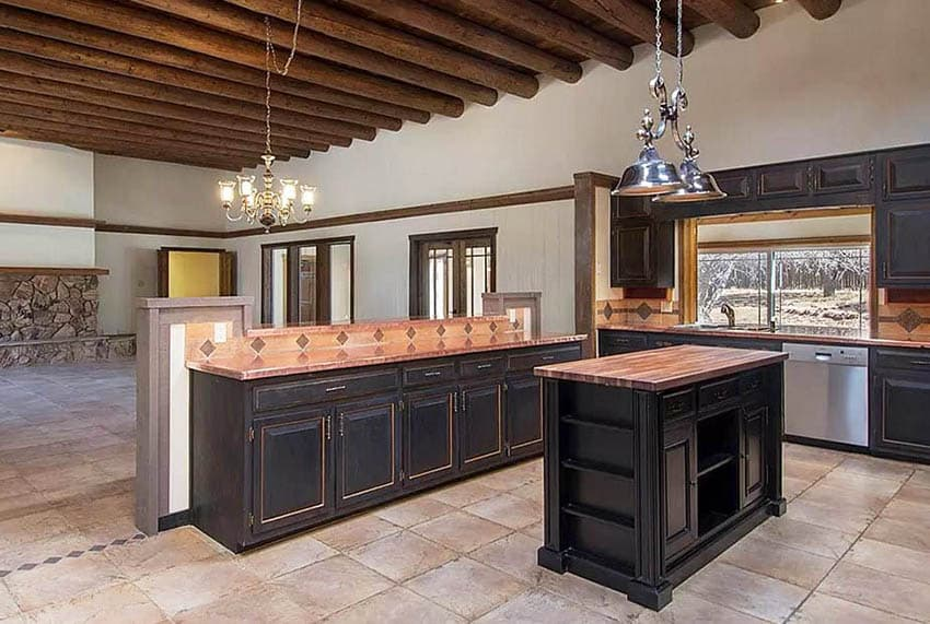 Kitchen with copper countertops, butcher block island and dark wood cabinets