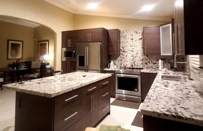 Kitchen with dark cabinets and light onyx countertops