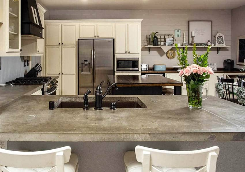 Kitchen with diy poured concrete countertops and cream cabinets