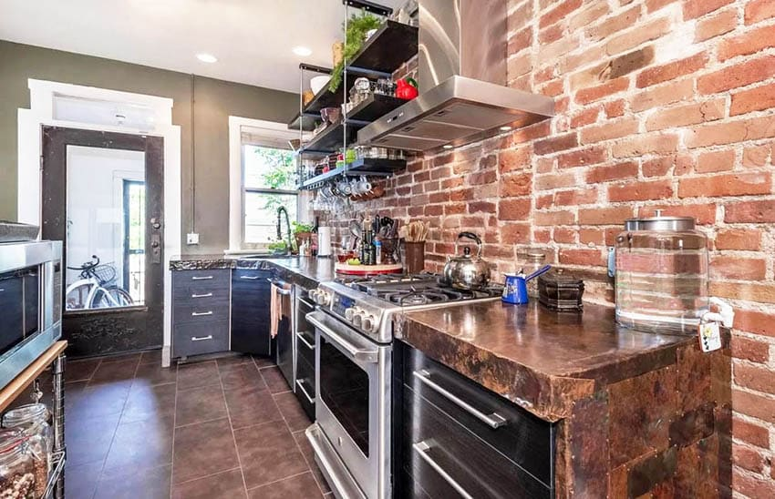 Kitchen with hammered copper counters, dark cabinets and brick accent wall