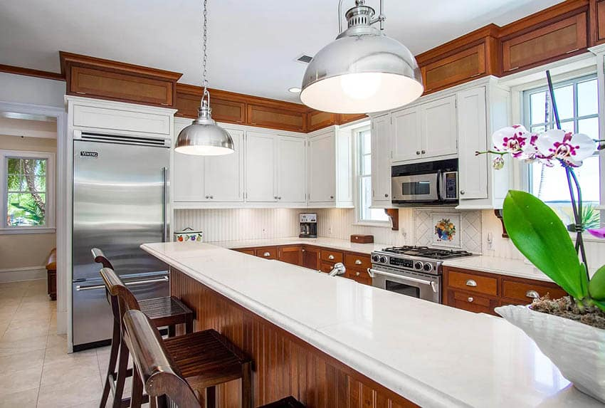 Kitchen with limestone countertops and stained wood and painted white cabinets