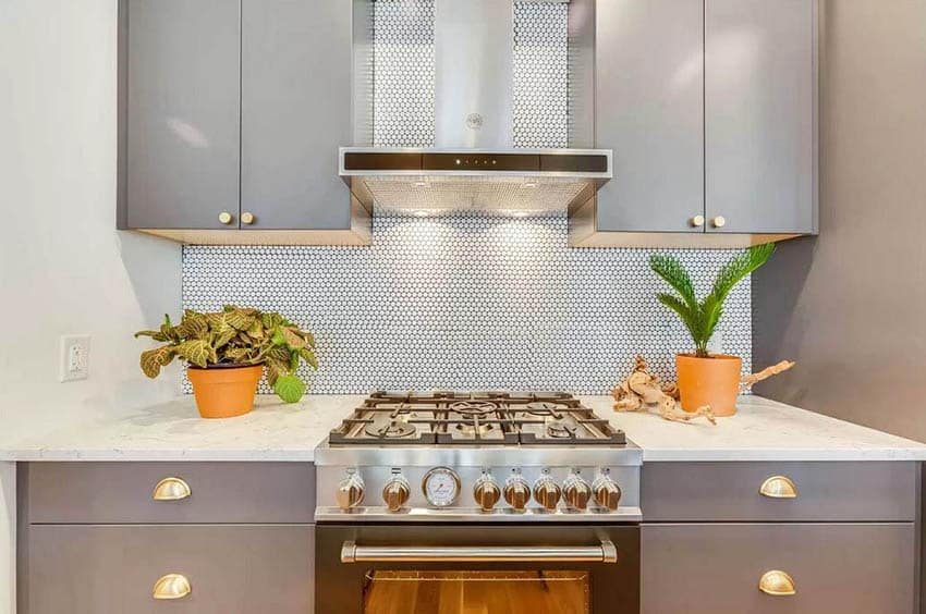 Kitchen with marble countertop and penny tile backsplash with gray cabinets