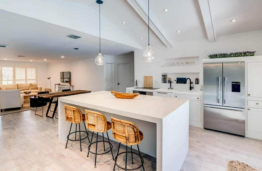 Kitchen with white concrete countertops and waterfall island