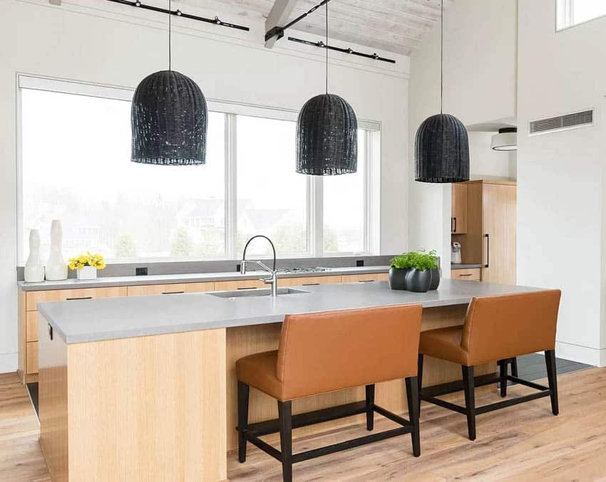 Modern kitchen with gray concrete counters and light wood cabinets