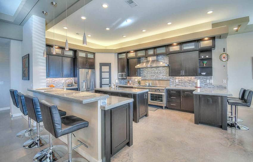Open concept kitchen with concrete countertops, breakfast bar, island and dark cabinets