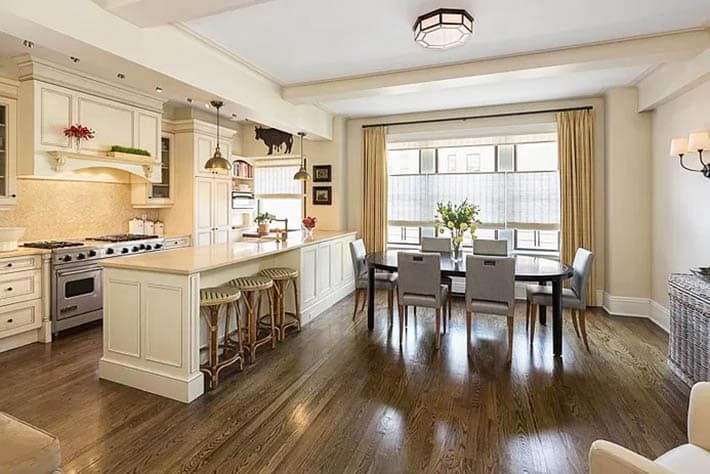 Open concept kitchen with cream cabinets and limestone countertops