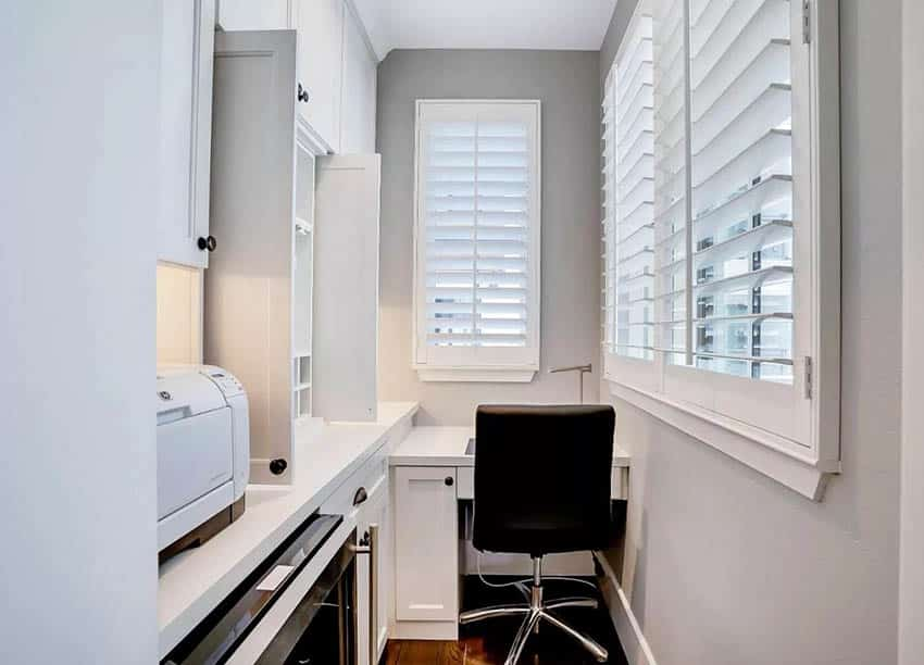 Small home office with built in desk white cabinets plantation shutters