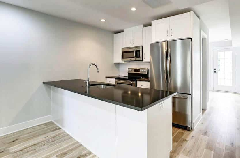 Small kitchen with white cabinets peninsula black countertops white subway tile backsplash