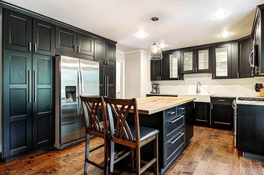 Traditional kitchen with black cabinets, wood countertop island and hardwood flooring