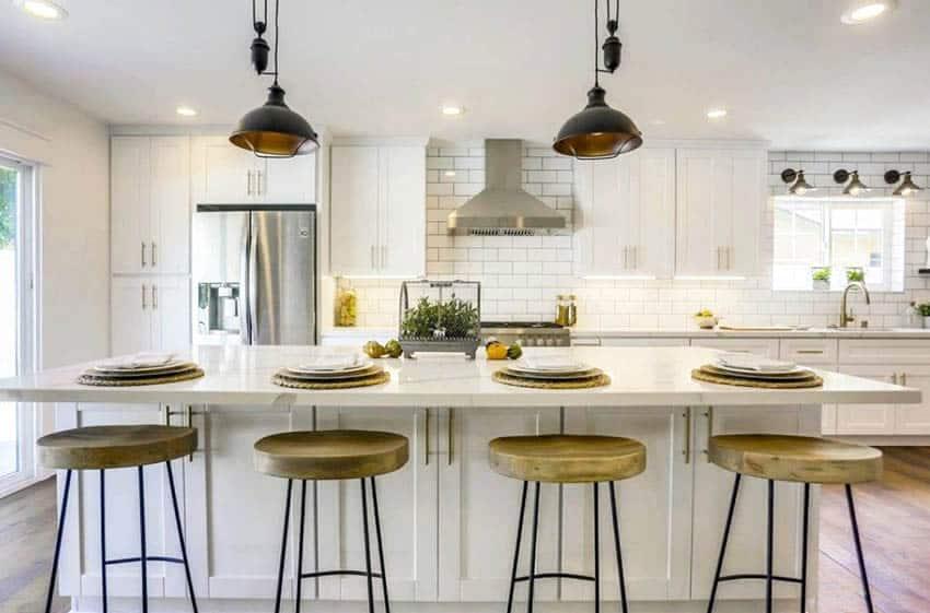 Transitional kitchen with white subway tile backsplash, quartz countertops and large island