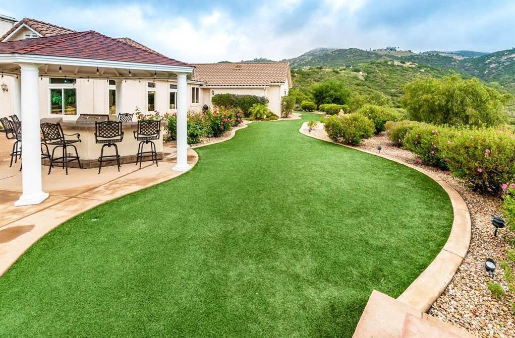 Backyard artificial grass design with outdoor kitchen