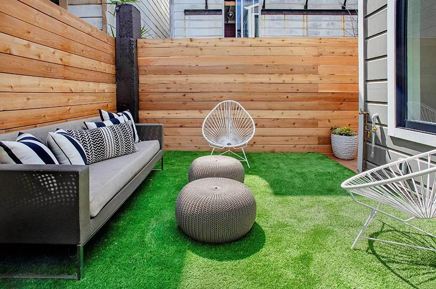 Backyard fenced in patio with artificial grass sitting area