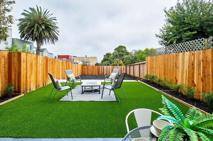 Backyard patio with fake grass rug and outdoor sitting area
