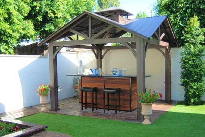 Backyard pavilion with stone patio and artificial grass