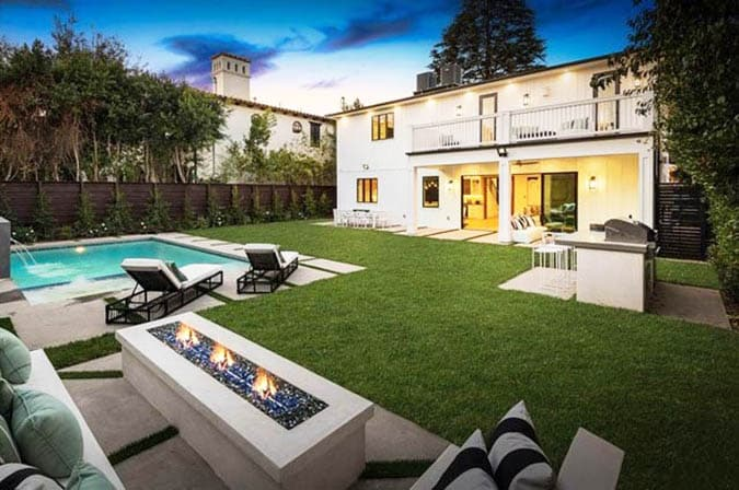 Backyard sitting area with fire pit and artificial grass around pool
