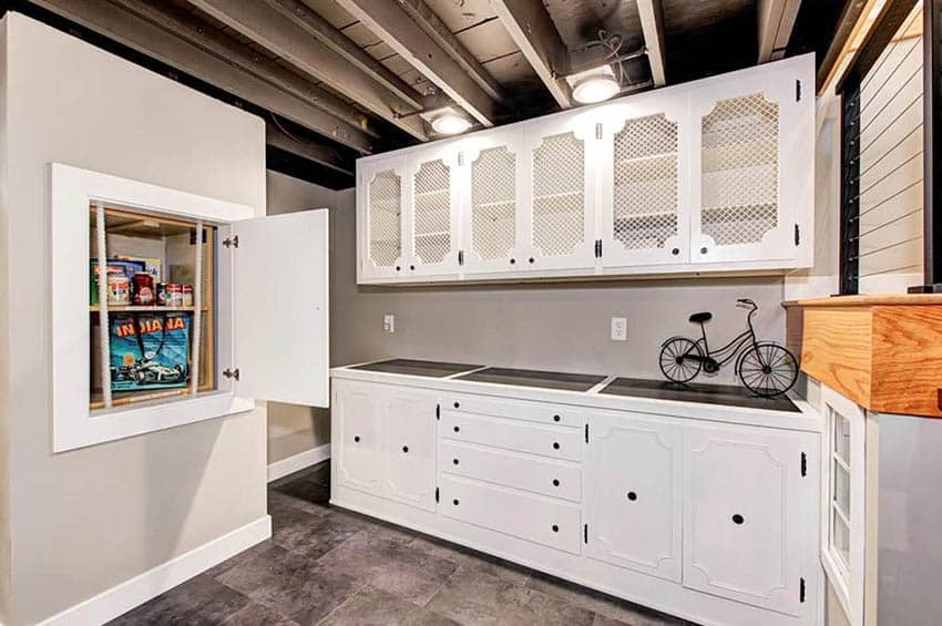 Basement pantry with manual dumbwaiter and white cabinets