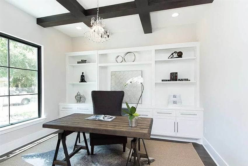 Beautiful home office with white cabinets, chandelier, wood beams and black framed picture window