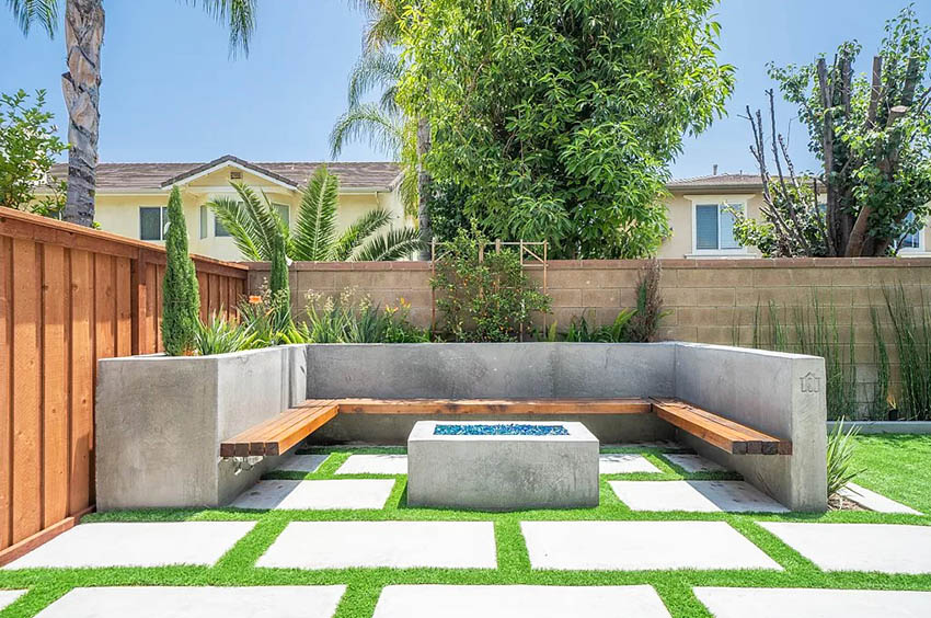 Concrete patio with bench fire pit and artificial grass