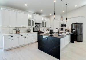 Contemporary kitchen with black quartz countertop island, white quartz and white cabinets