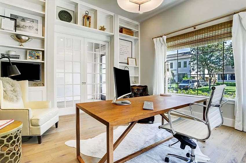 Home office with built in bookshelves above french doors