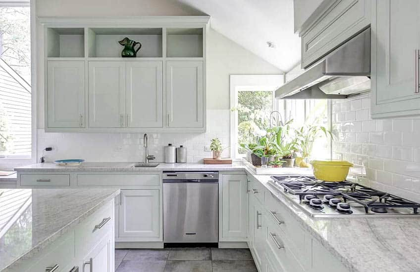 Inviting kitchen with corner window, light green cabinets and white granite countertops