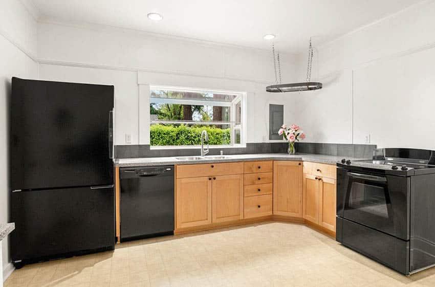 L shaped kitchen with garden window black appliances