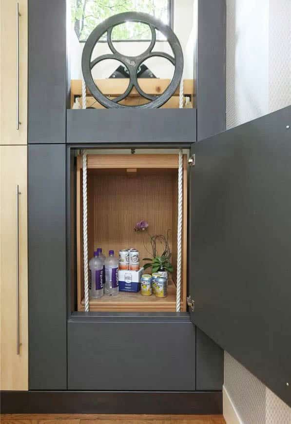 Manual dumbwaiter with large flywheel pulley and rope pulls