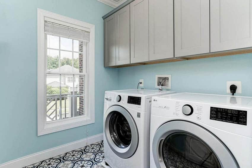Pretty laundry room with front load washer dryer built in cabinets