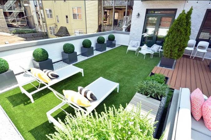 Rooftop patio with artificial grass and lounge chairs