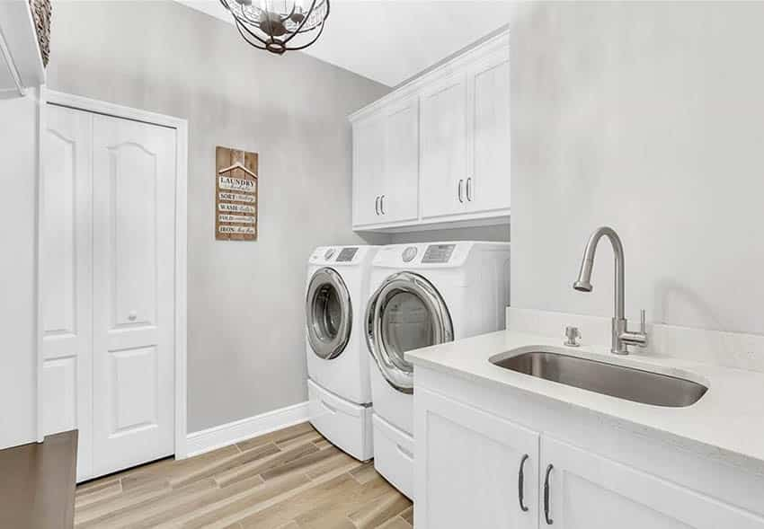 Stylish laundry room with front load washer and dryer with built in cabinets