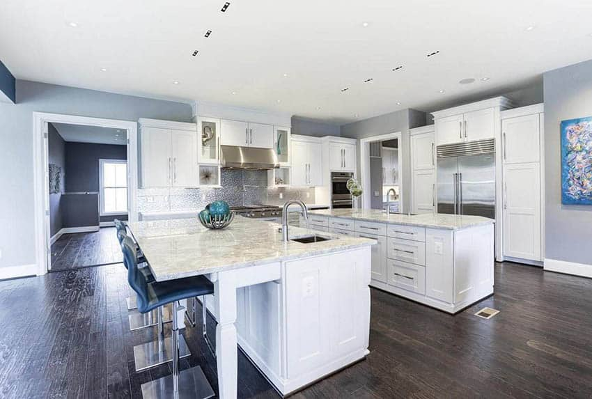 All white kitchen with two islands marble countertops wood flooring
