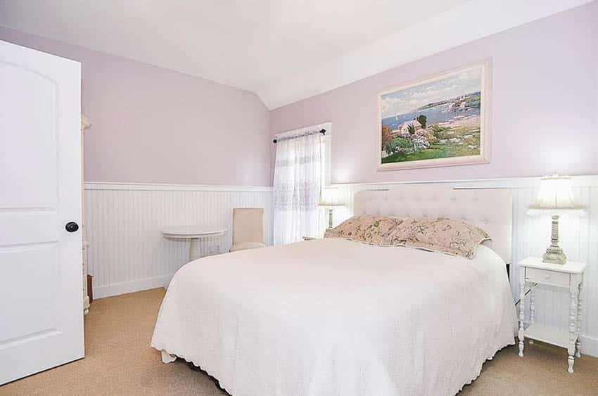 Bedroom with pink paint and white wainscoting