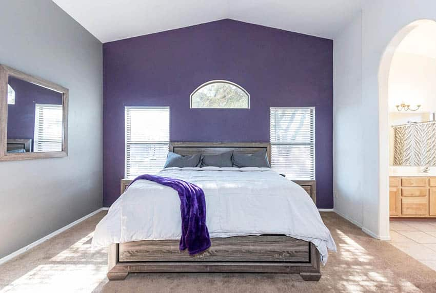 Bedroom with purple and gray accent walls, gray pillows and purple blanket