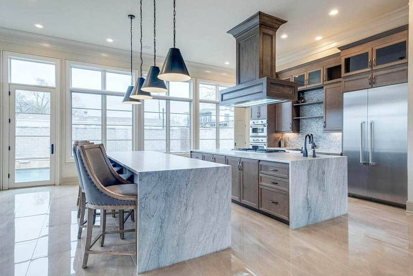 Contemporary gourmet kitchen with two quartz islands with stovetop sink custom range hood pendant lights