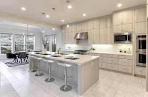 Contemporary kitchen with bleached color cabinets under cabinet lighting white quartz countertops