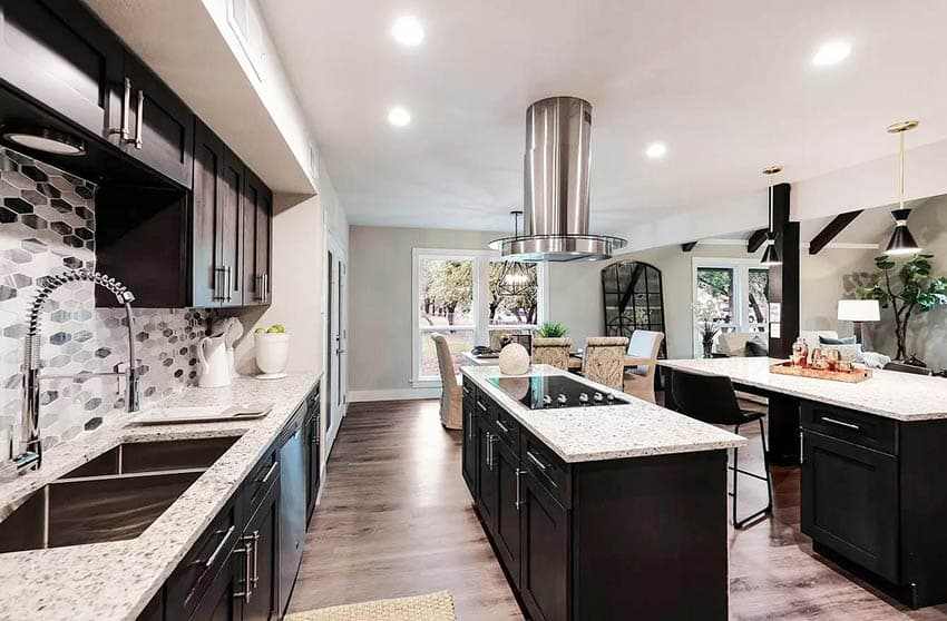 Contemporary kitchen with two islands built in stove top dark cabinets white quartz counters
