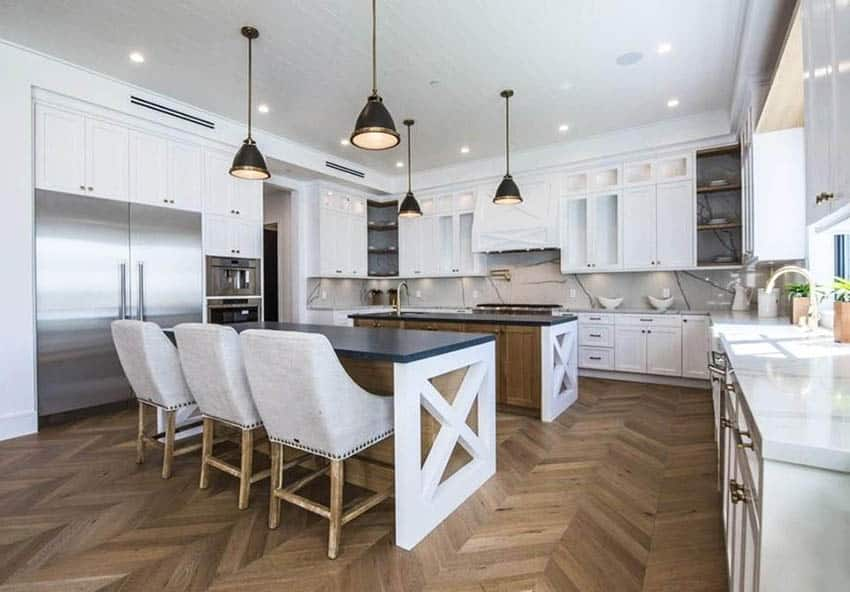 Contemporary kitchen with two large islands wood base black quartz counters white main cabinets