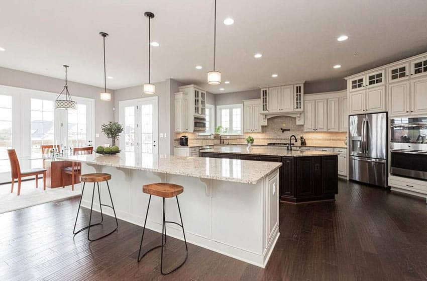 Kitchen with off white cabinets two islands beige granite countertops
