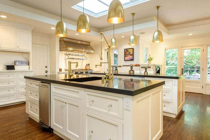 Kitchen with two islands with black quartz countertops white cabinets gold pendant lights