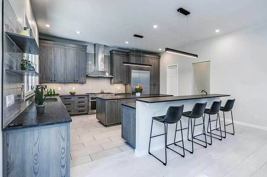 Large kitchen with two islands with breakfast bar linear light fixture wood grain cabinets