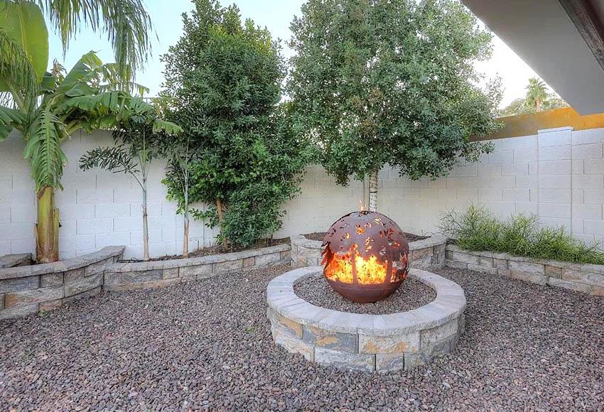 Lava rock gravel backyard with custom globe fire pit